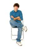 Junger Mann, der im Stuhl sitzt stockfotos