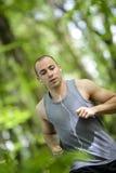 Junger Mann, der im Wald läuft stockbild