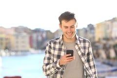 Junger Mann, der intelligentes Telefon geht und verwendet stockfotografie