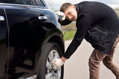 Junger Mann, der kämpft, um den Reifen auf seinem Auto zu ändern Stockbilder