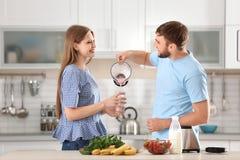 Junger Mann, der köstlichen Milchshake in Glas in der Küche gießt lizenzfreies stockbild