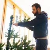 Junger Mann, der künstlichen Weihnachtsbaum anbringt Lizenzfreie Stockbilder