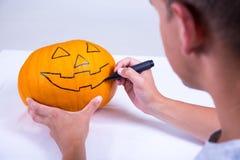 Junger Mann, der Kürbis für Halloween zubereitet Lizenzfreie Stockfotos