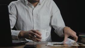Junger Mann, der Kaffee auf Papieren beim Arbeiten mit Laptop-PC im Büro verschüttet Langsame Bewegung stock video footage