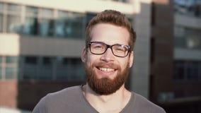 Junger Mann, der Kamera lächelt und betrachtet Porträt des glücklichen hübschen jungen Kerls in der städtischen Straße Mann berüh stock video footage