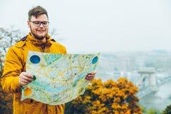 Junger Mann, der Karte in den Händen am Herbsttag hält stockfotos