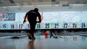 Junger Mann, der Kegelbowlingspiel spielt und Bowlingkugel an den Stiften im Weg bei Wangsa wirft stock video