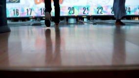 Junger Mann, der Kegelbowlingspiel und die Bowlingkugel im Weg werfen spielt Abschluss herauf hintere Beinansicht Stativgesamtlän stock video footage