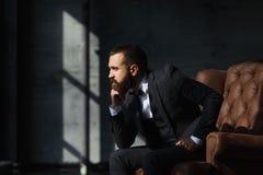 Junger Mann in der Klage, die auf Sofa stillsteht lizenzfreies stockfoto
