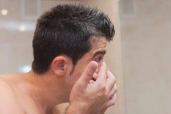 Junger Mann, der Kontaktlinse in sein Auge einsetzt stockfoto