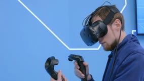 Junger Mann, der Kopfhörer der virtuellen Realität verwendet und mit speziellem Steuerknüppel zeichnet lizenzfreies stockbild
