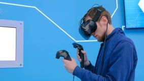 Junger Mann, der Kopfhörer der virtuellen Realität verwendet und mit speziellem Steuerknüppel zeichnet stockfotos