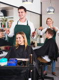 Junger Mann, der langes Haar des schönen Mädchens schneidet Lizenzfreie Stockfotos
