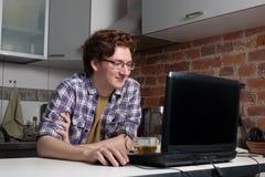 Junger Mann, der an Laptop arbeitet stockbild