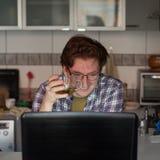 Junger Mann, der an Laptop arbeitet stockfotografie