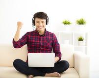 junger Mann, der Laptop-Computer mit Kopfhörer verwendet stockbild