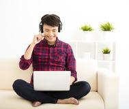 junger Mann, der Laptop-Computer mit Kopfhörer verwendet Stockfotografie