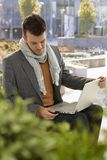 Junger Mann, der Laptop im Park verwendet Lizenzfreie Stockfotos