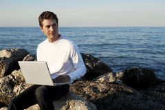 Junger Mann, der Laptop am Strand verwendet Stockfotos