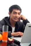 Junger Mann, der Laptop verwendet Stockfoto