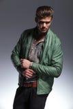 Junger Mann in der Lederjacke, die seinen Ärmel repariert Stockfotos