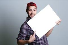Junger Mann, der leeres Papier in einem Studio hält lizenzfreie stockfotos
