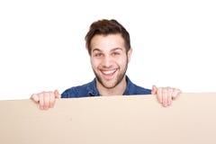 Junger Mann, der leeres Plakat hält Stockfotografie