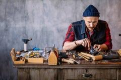 Junger Mann, der lernt, mit Metall im Juweliergeschäft zu arbeiten lizenzfreie stockbilder