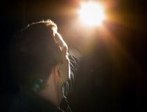 Junger Mann, der am Licht in der Dunkelheit die Hauptrolle spielt Lizenzfreie Stockfotografie