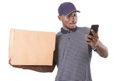 Junger Mann der Lieferung in der roten Uniform lokalisiert auf wei?em Hintergrund lizenzfreies stockbild