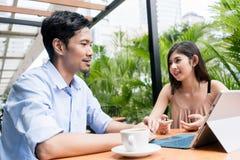 Junger Mann, der on-line-Inhalt beim Sitzen mit einer jungen Frau aufpasst lizenzfreie stockbilder