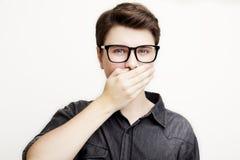 Junger Mann, der lokalisiert auf Weiß mit Brillen verwechselt glaubt Lizenzfreies Stockfoto