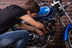 Junger Mann, der manuell sein Motorrad repariert Stockfotos