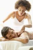 Junger Mann, der Massage am Badekurort genießt Stockbilder