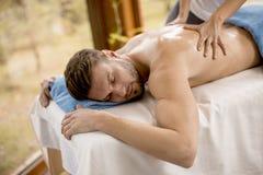 Junger Mann, der Massage im Badekurort hat Stockbild
