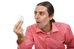 Junger Mann, der mit überraschten Blicken an einer Glühlampe ist Lizenzfreies Stockbild