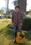 junger Mann, der mit der Akustikgitarre in einem Park aufwirft lizenzfreie stockfotos