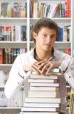 Junger Mann, der mit Büchern sitzt Stockfotografie