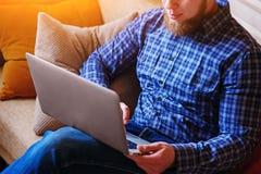 Junger Mann, der mit Computer auf dem Strand arbeitet Gut aussehender Mann, der mit dem Laptop legt auf die Couch am Strand arbei Lizenzfreie Stockfotografie