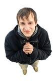 Junger Mann, der mit dem Plädieren des Blickes auf Weiß steht Stockfotografie