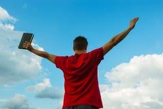 Junger Mann, der mit den angehobenen Händen bleibt Lizenzfreie Stockfotografie