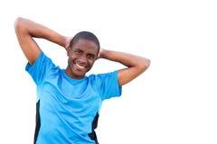 Junger Mann, der mit den Händen hinter Kopf auf lokalisiertem weißem Hintergrund lächelt stockfotos