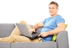 Junger Mann, der mit einem Computer gesetzt auf Sofa sich entspannt Stockfotografie