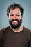 Junger Mann, der mit einem dunklen Bart lächelt Stockfotografie