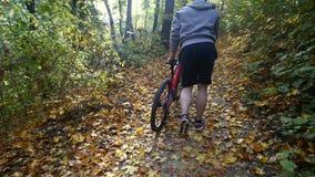 Junger Mann, der mit einem Fahrrad im Herbstpark geht stock footage