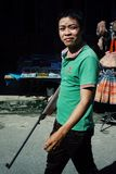 junger Mann, der mit einem Gewehr am Markt geht stockfoto