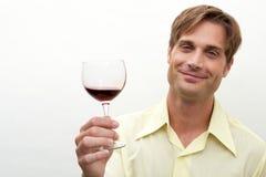 Junger Mann, der mit einem Glas röstet Stockfotografie