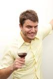 Junger Mann, der mit einem Glas röstet Stockbilder