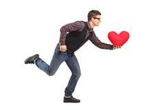 Junger Mann, der mit einem roten Kissen in seiner Hand läuft Lizenzfreie Stockbilder