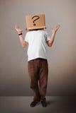 Junger Mann, der mit einem Sammelpack auf seinem Kopf mit questi gestikuliert Lizenzfreie Stockfotografie